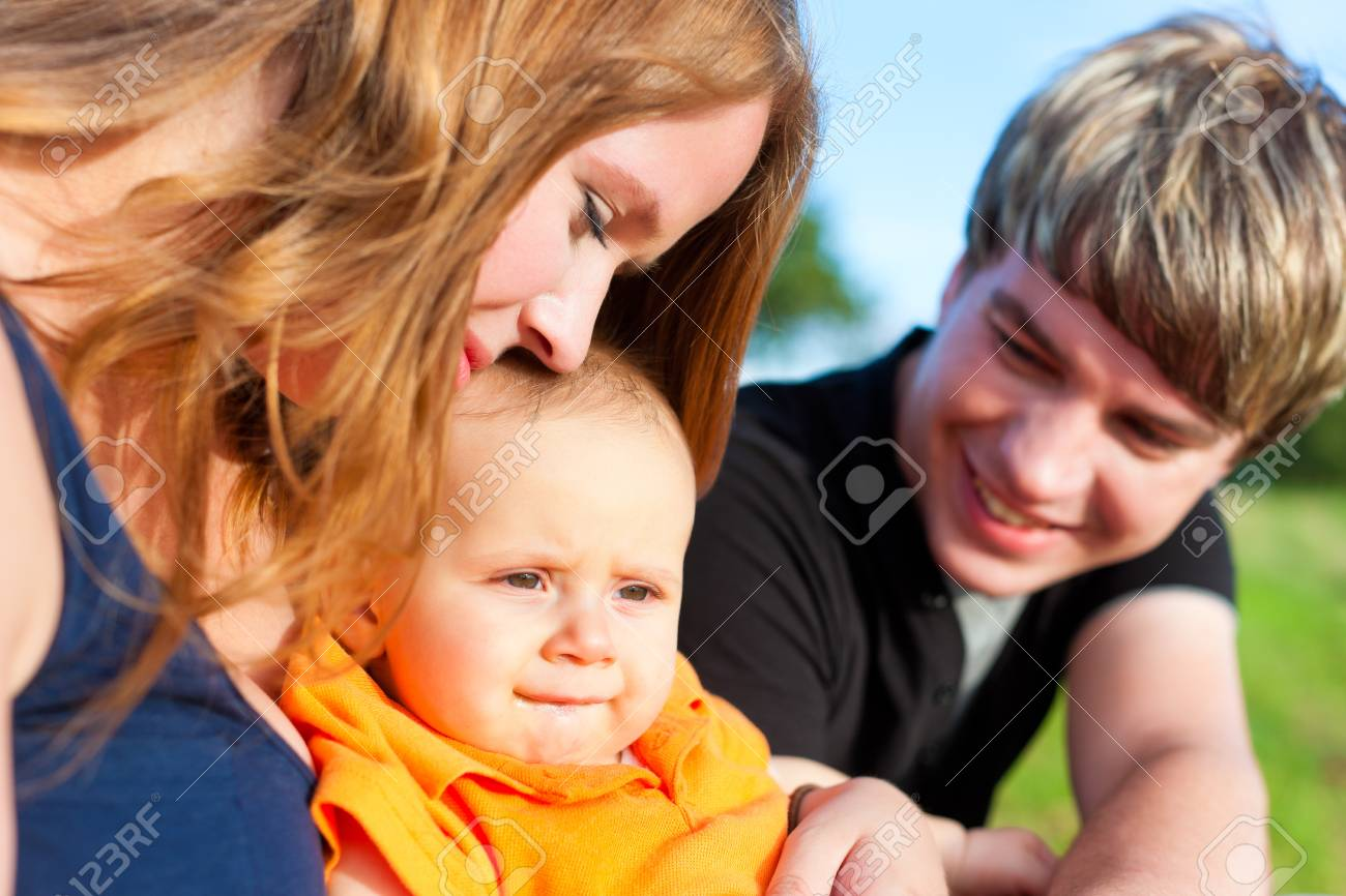 Family - mother, father and child sitting and playing in garden Stock Photo - 12718861