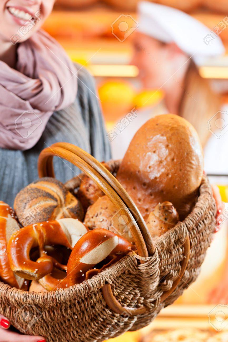 Female customer standing with breadbasket and fresh bread and rolls in bakery Stock Photo - 12718863