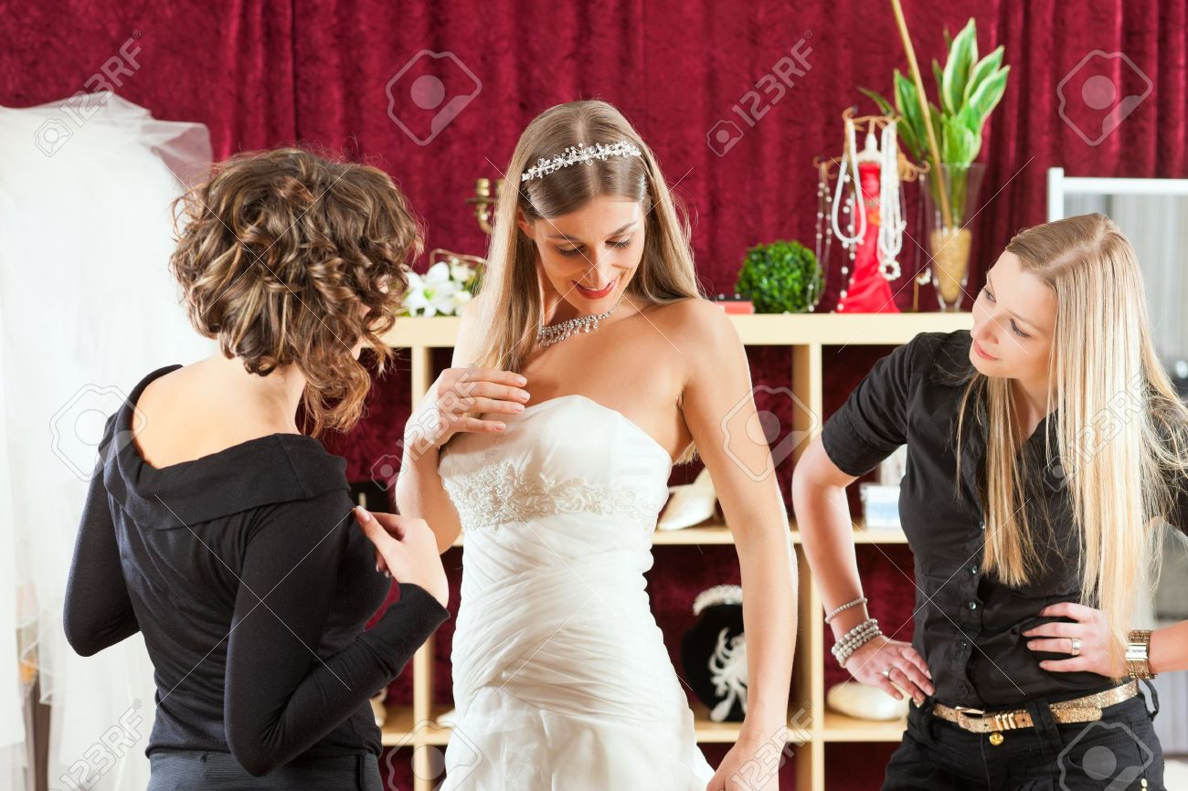 Bride At The Clothes Shop For Wedding Dresses; She Is Choosing ...