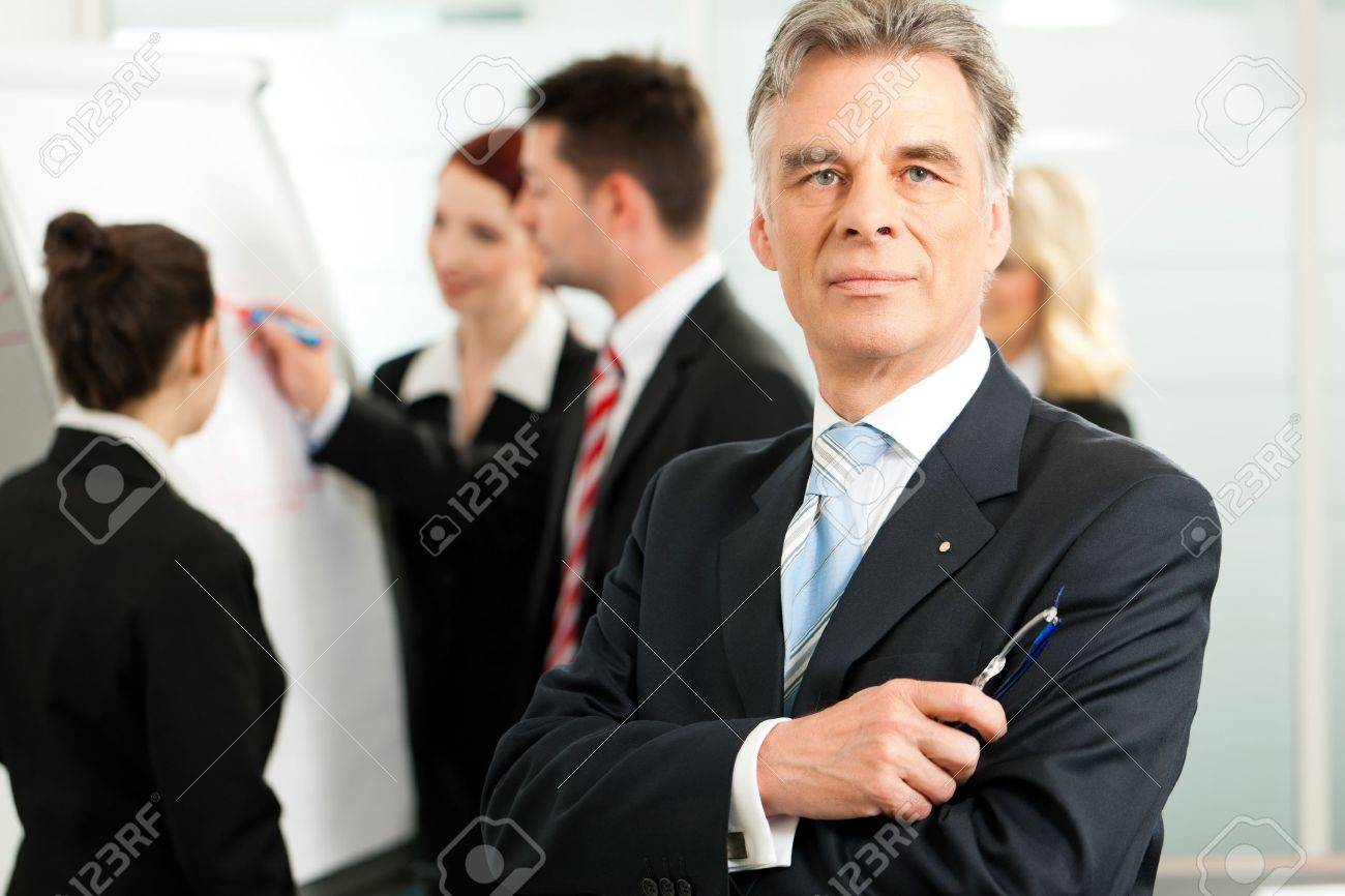 Business - team in an office; the senior executive is standing in front Standard-Bild - 12719131