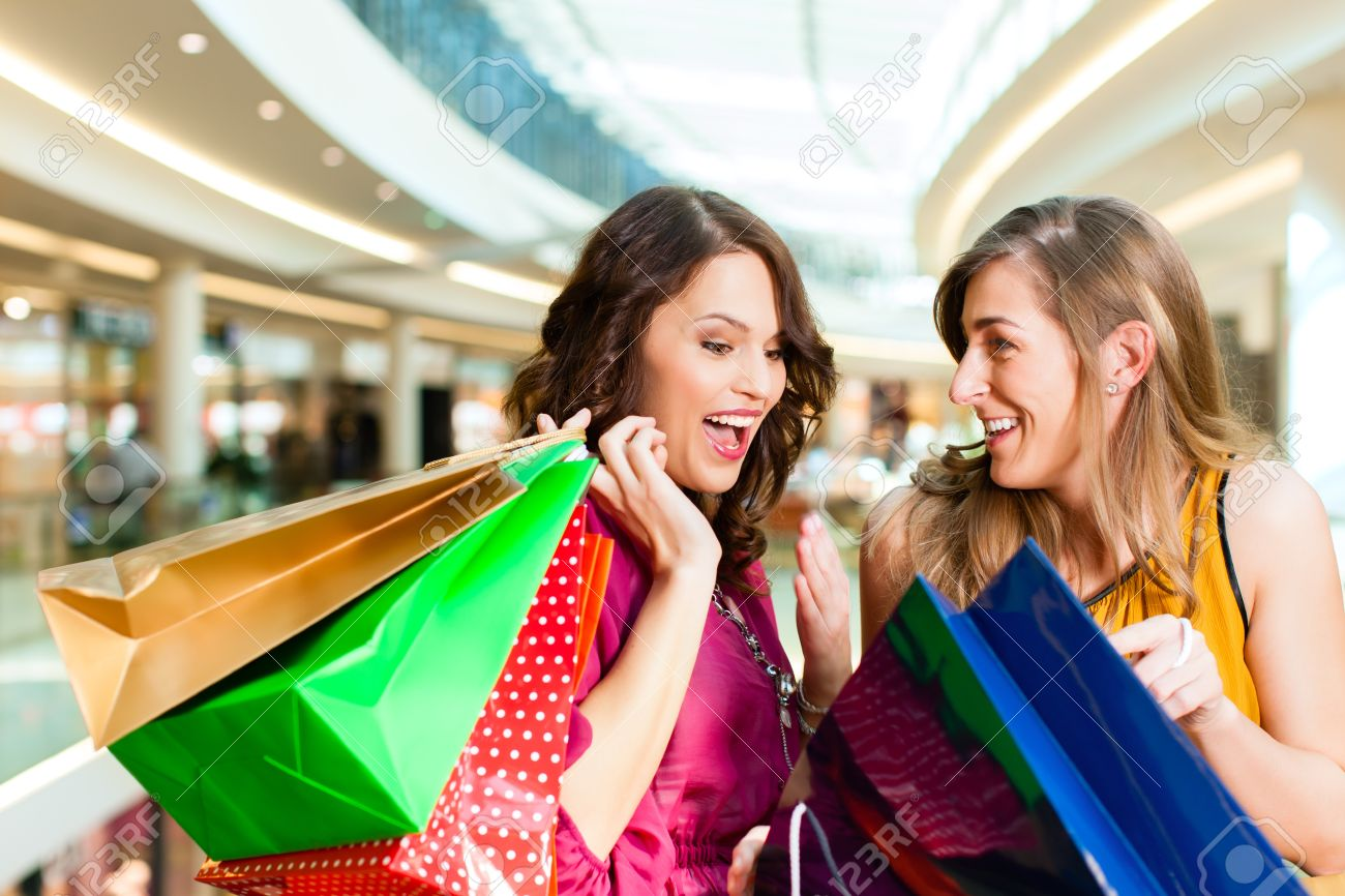 Two female friends with shopping bags having fun while shopping in a mall Stock Photo - 13190902