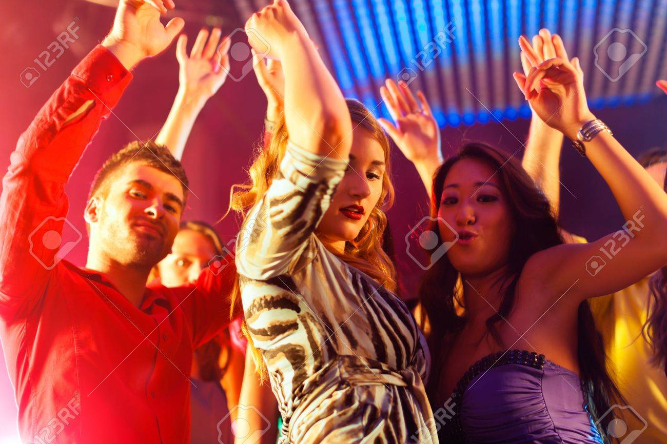 Group of party people - men and women - dancing in a disco club to the music Stock Photo - 13452908