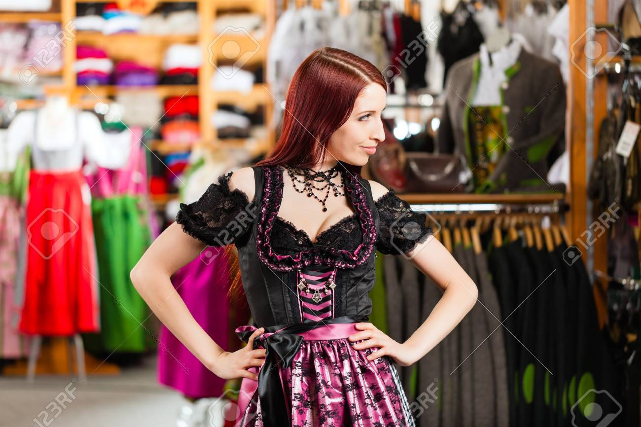 bb3bdc3c6ef Stock Photo - Traditional clothes - young woman is buying Tracht or dirndl  in a shop