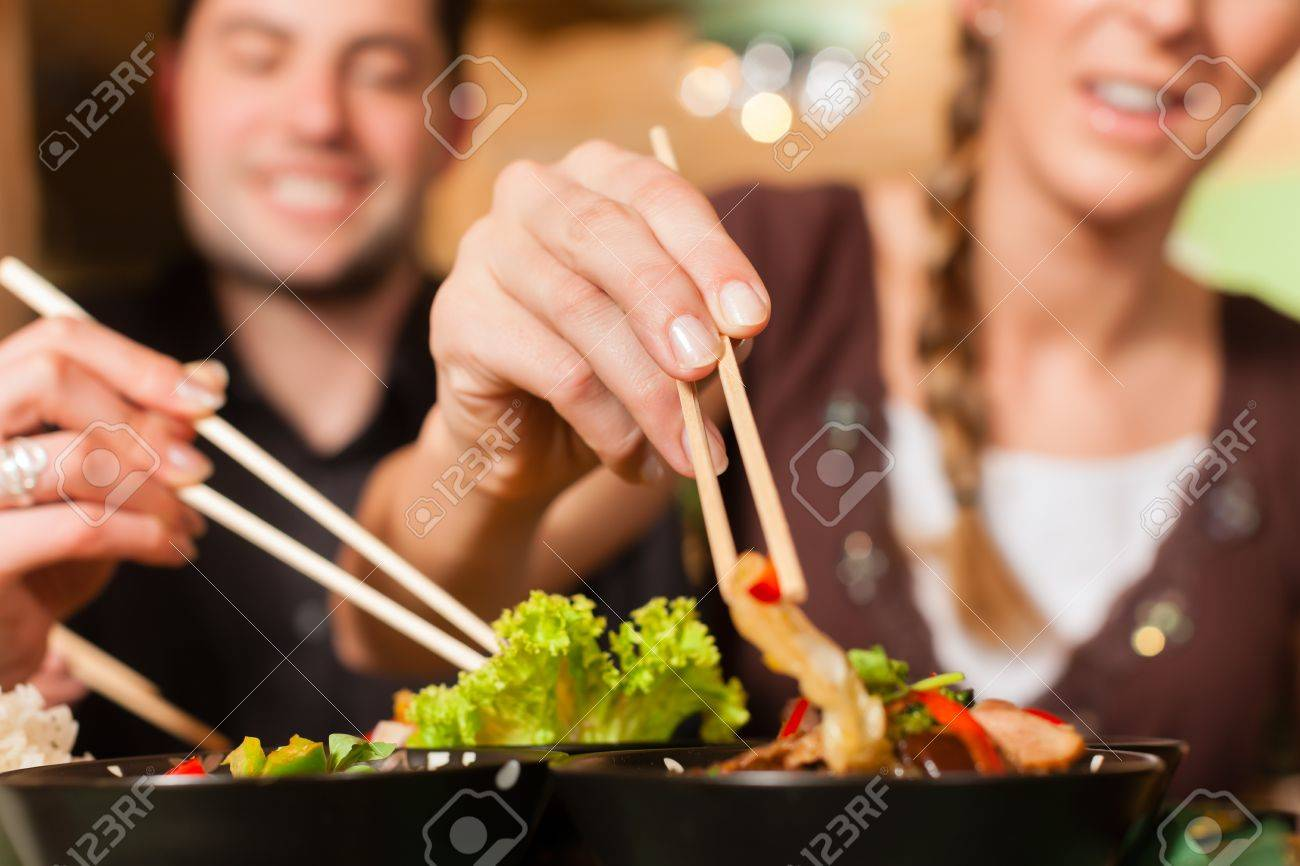Young people eating in a Thai restaurant; they eating with chopsticks Stock Photo - 13503285
