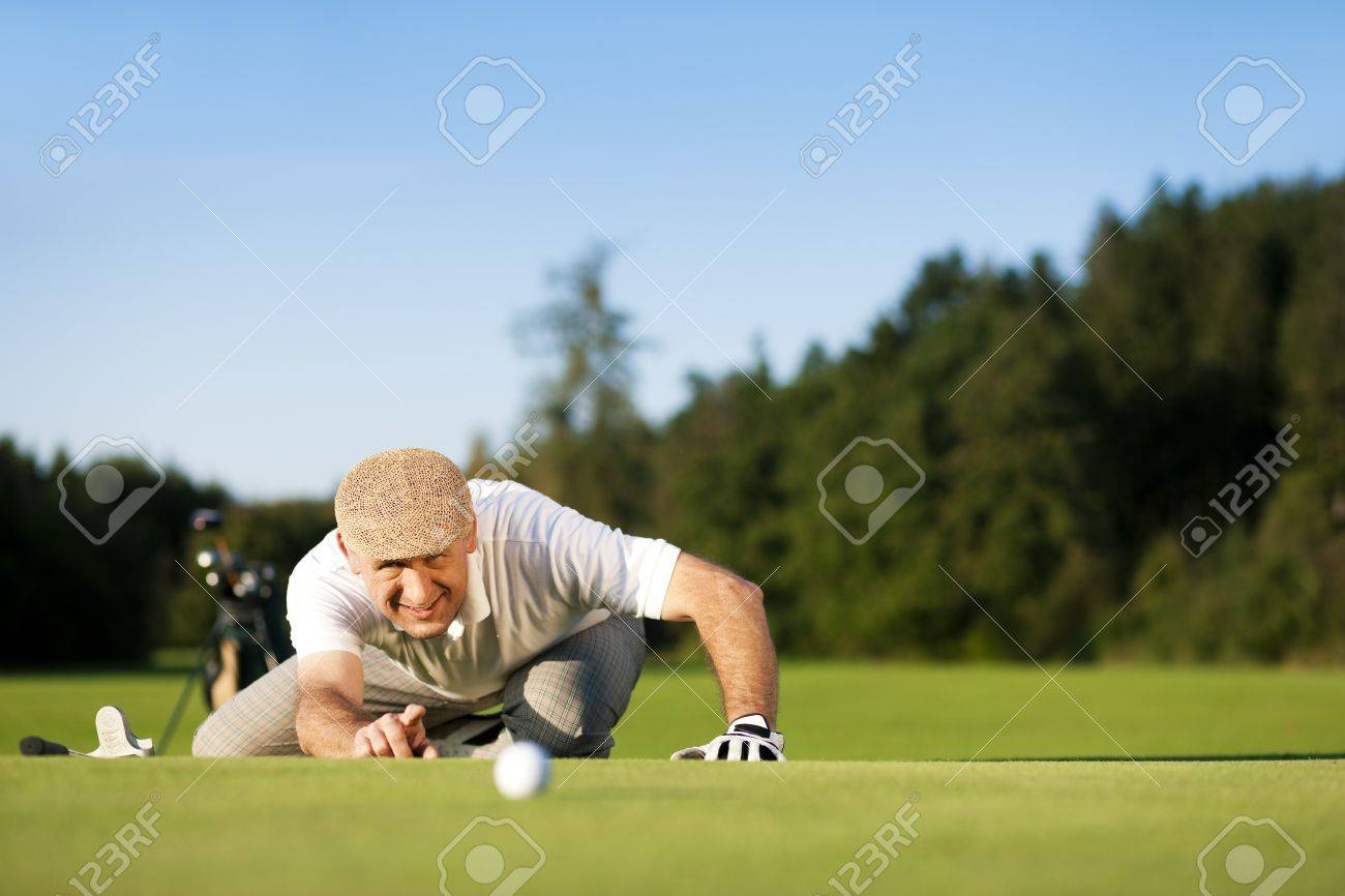 Senior man playing golf aiming for the hole, it is a wonderful clear summer late afternoon, the colors are very vivid Stock Photo - 14095510