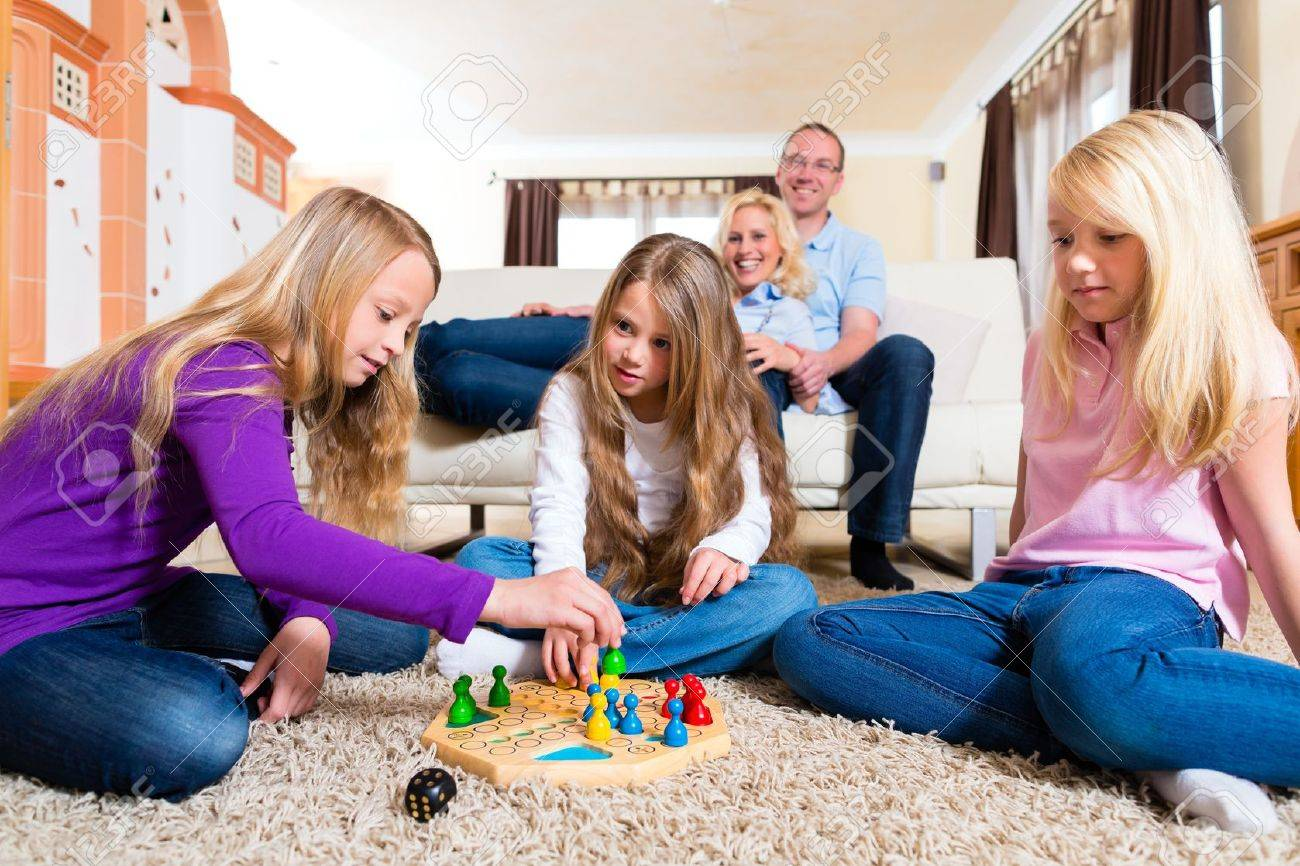 Family playing board game ludo at home on the floor Stock Photo - 14727932