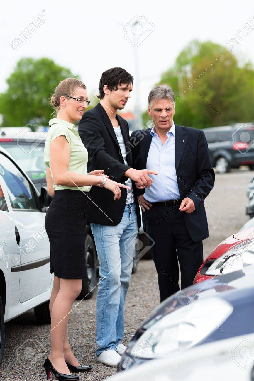 Mature car dealer and young couple standing on parking place at dealership in front of cars Stock Photo - 14727669