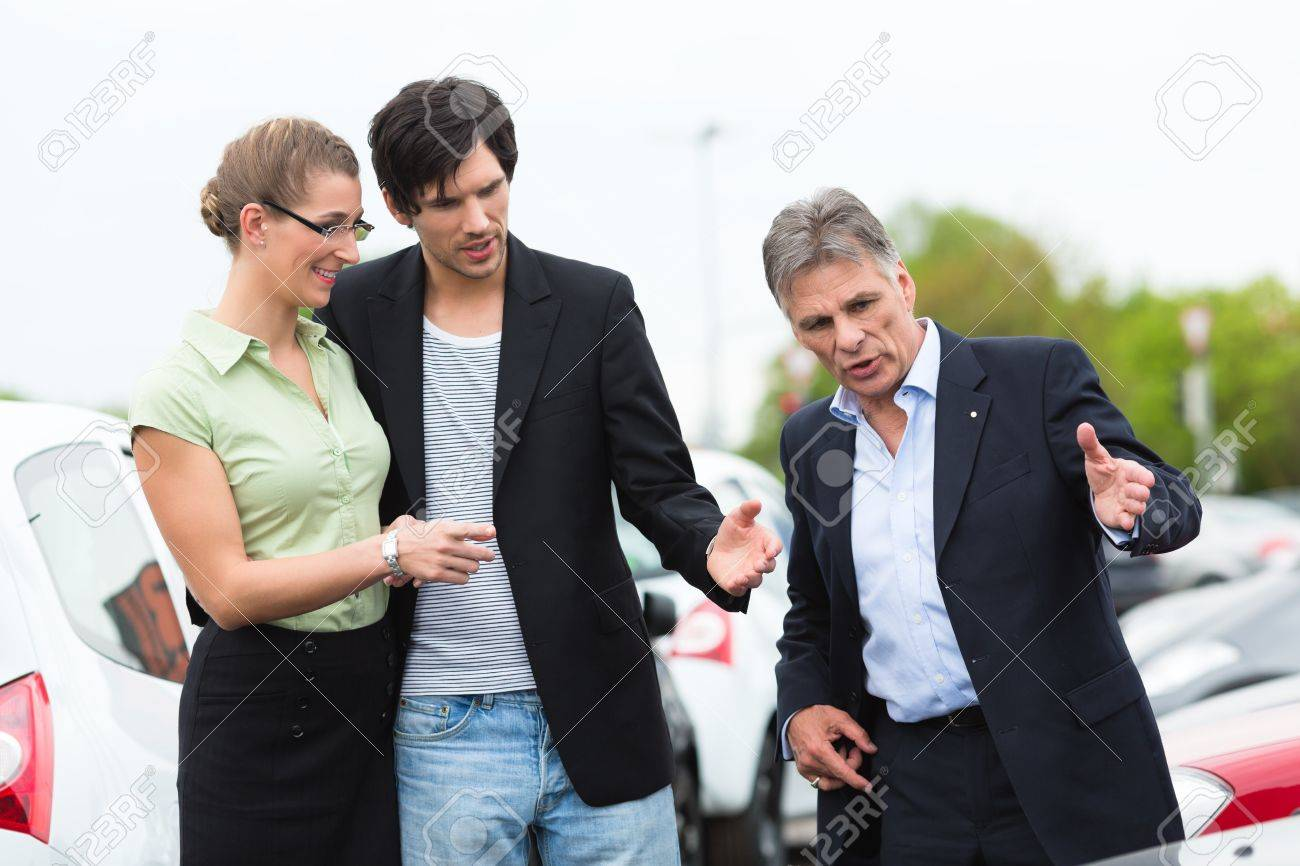 Mature car dealer and young couple standing on parking place at dealership in front of cars Stock Photo - 14727574