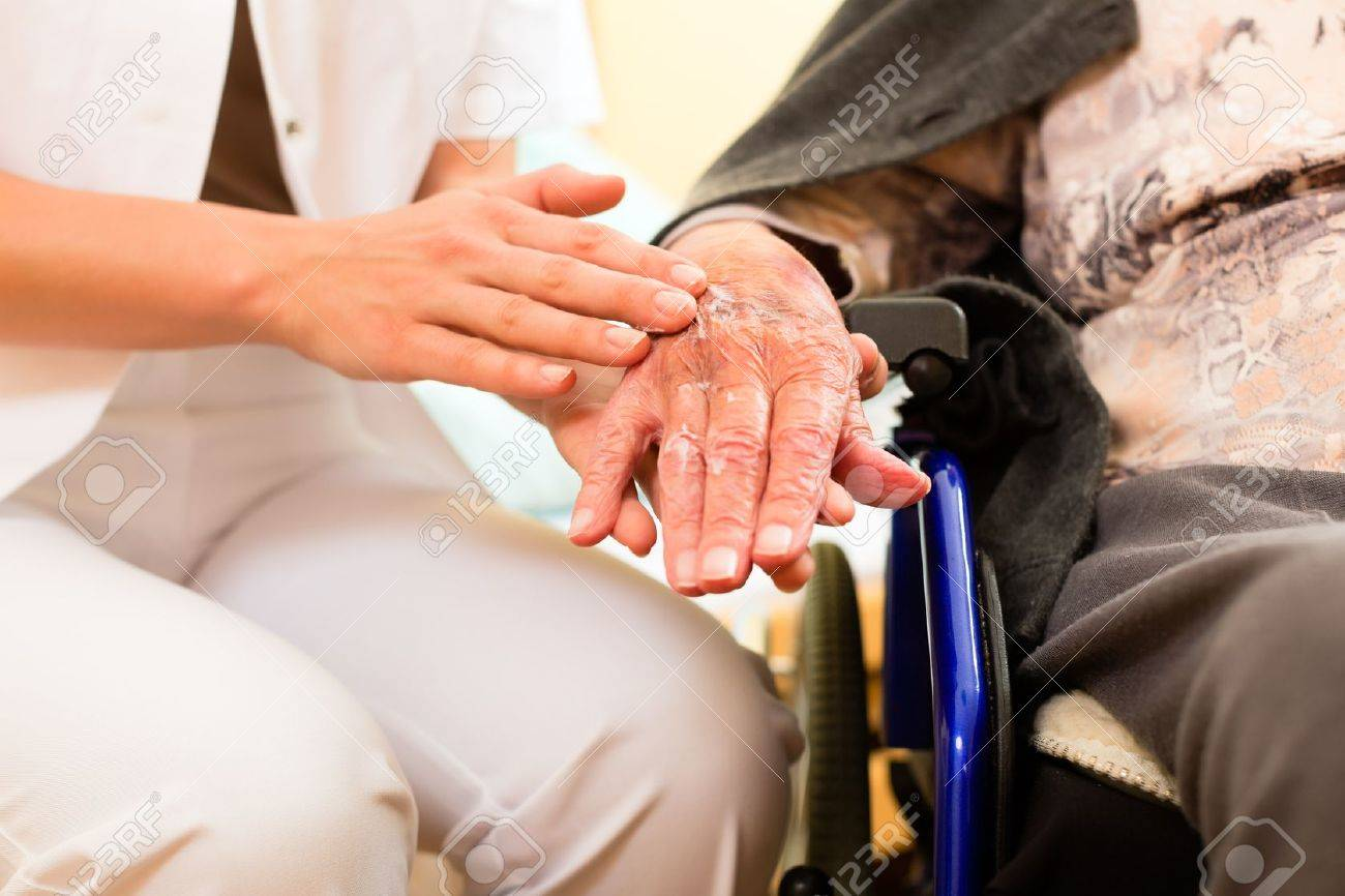 Young nurse and female senior in nursing home, the old lady sitting in a wheel chair Stock Photo - 14727623