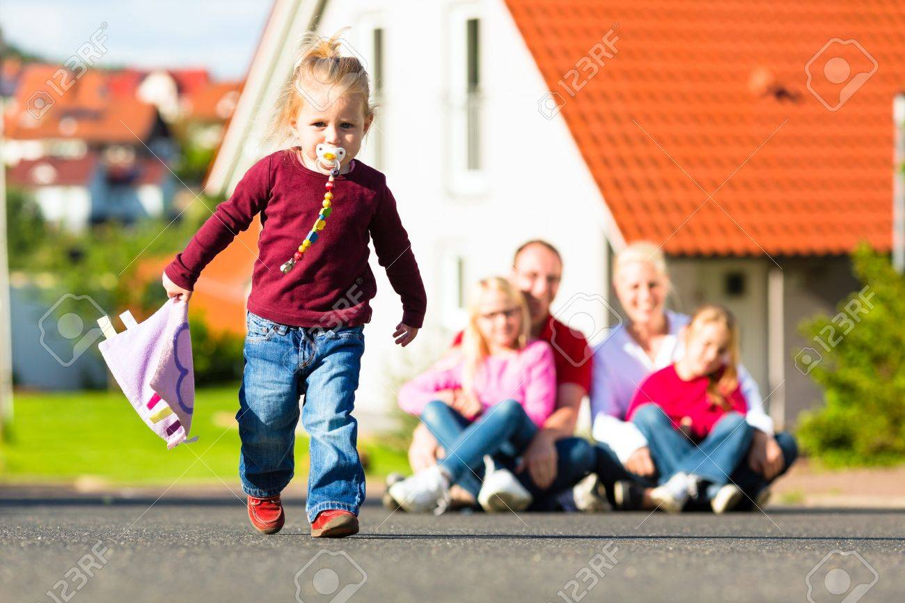 Young family sitting in the sun in front of their new home, their baby running in front Stock Photo - 15120573