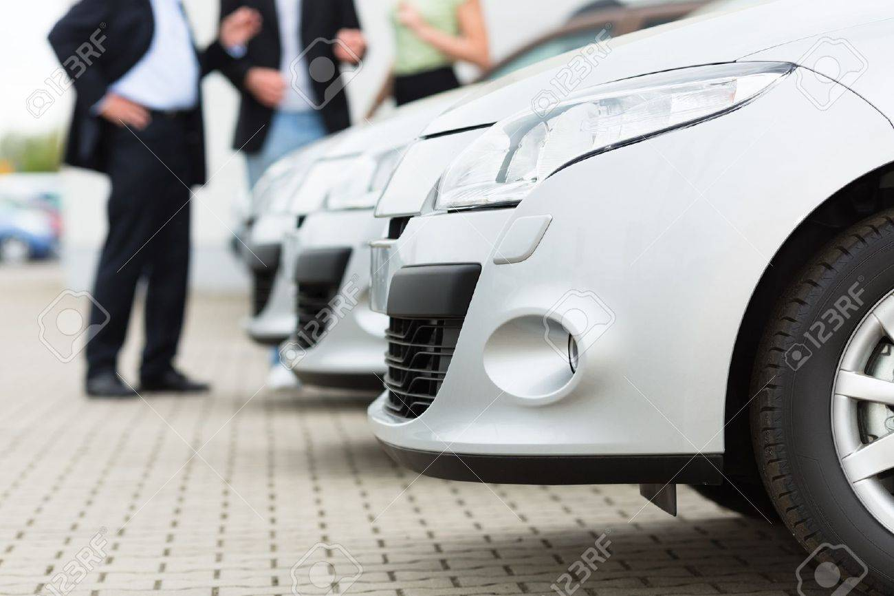 Two men man and one woman stand behind a row of silver-metallic cars on a parking place on yard of dealer Stock Photo - 15479921
