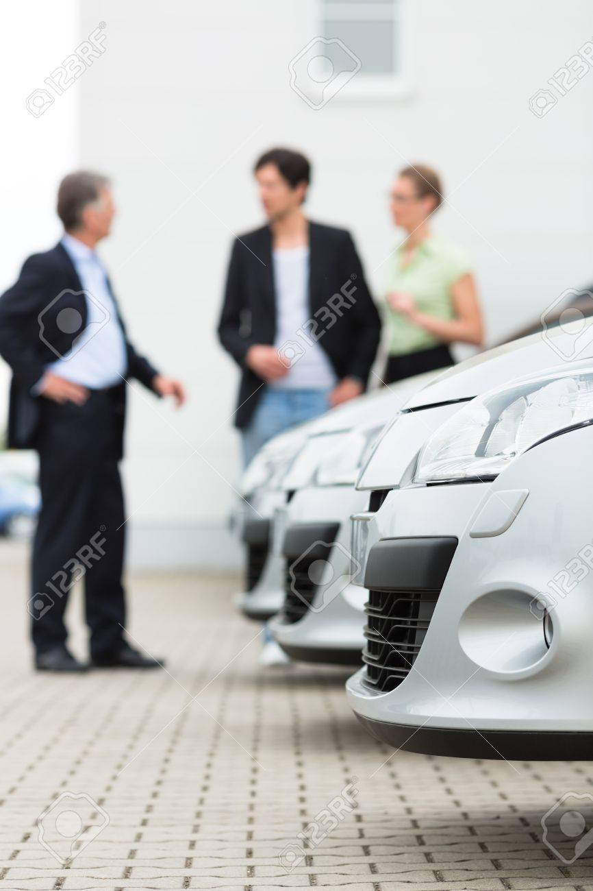 Two men man and one woman stand behind a row of silver-metallic cars on a parking place on yard of dealer Stock Photo - 15479972