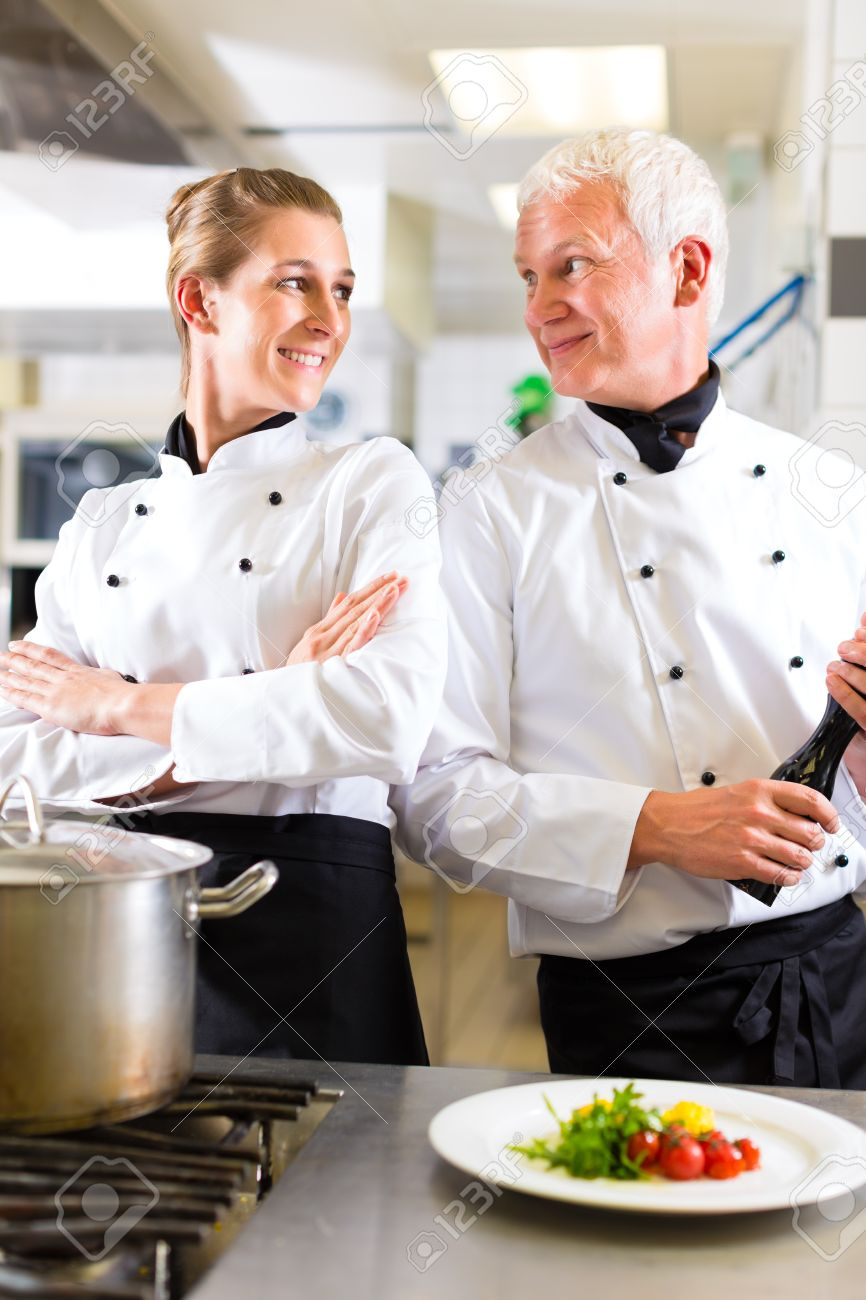 Two chefs - man and woman - in hotel or restaurant kitchen working and cooking in team Stock Photo - 15479900
