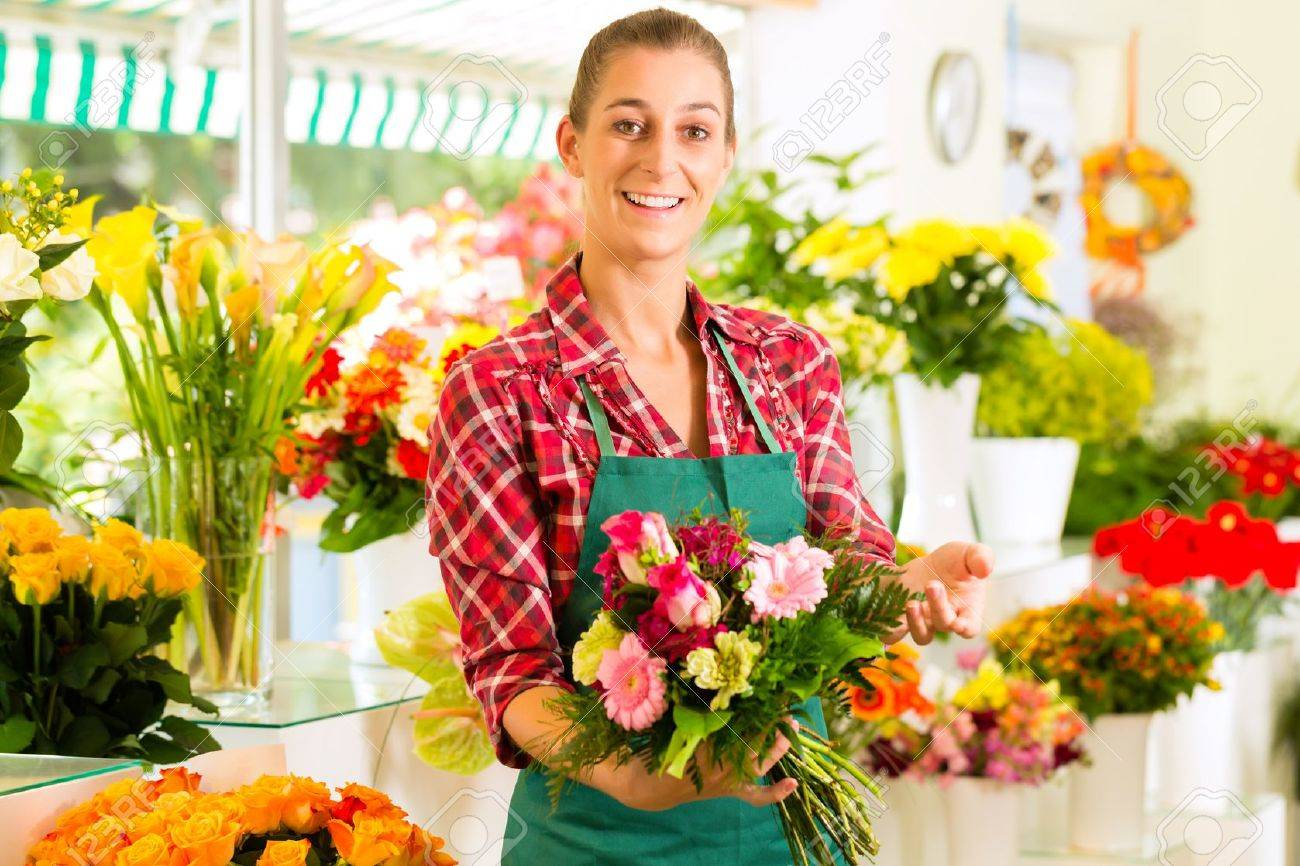 Female florist in flower shop or nursery presenting roses Stock Photo - 15479915