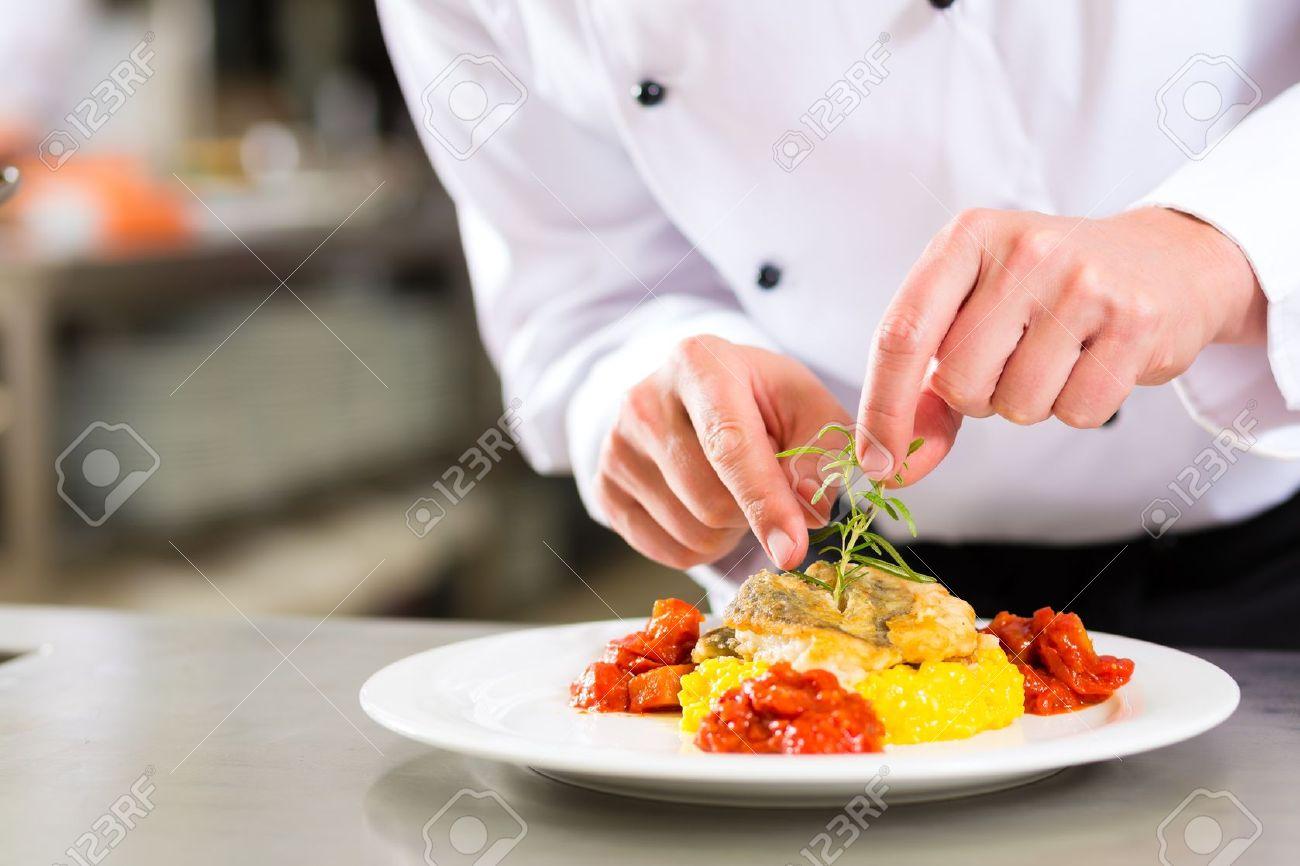 Restaurant Kitchen Chefs chef in hotel or restaurant kitchen cooking, he is finishing