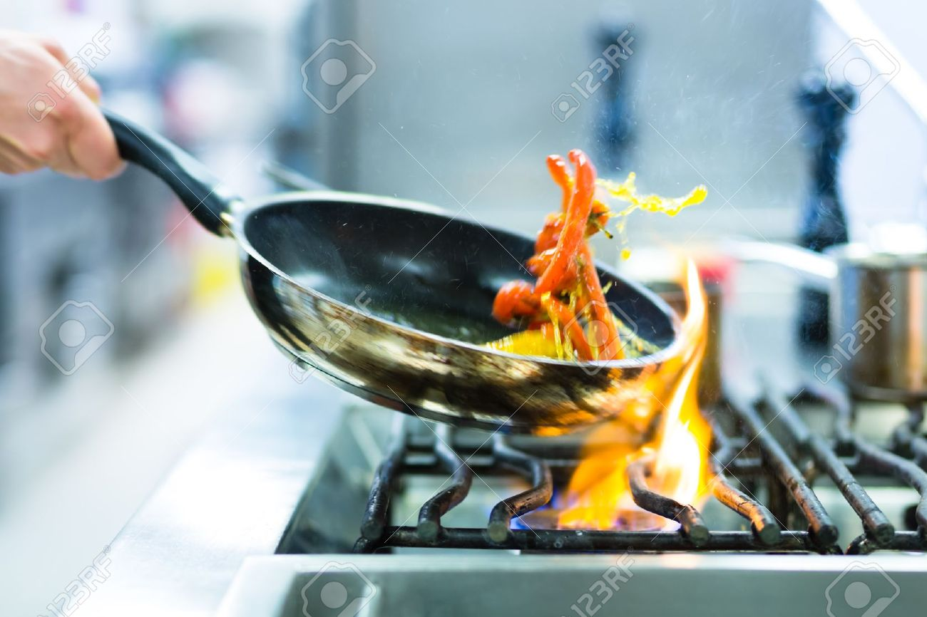 Chef In Restaurant Kitchen At Stove With Pan, Doing Flambe On ...