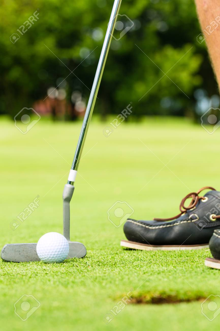 Golf player putting ball into hole, only feet and iron to be seen Stock Photo - 15678162