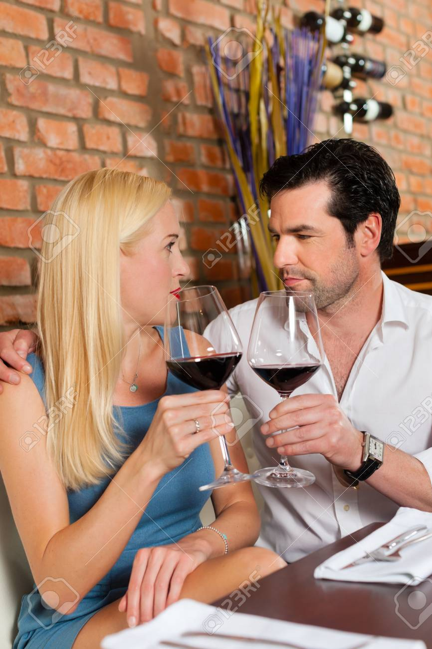 Attractive young couple drinking red wine in restaurant or bar, it might be the first date Stock Photo - 15785047