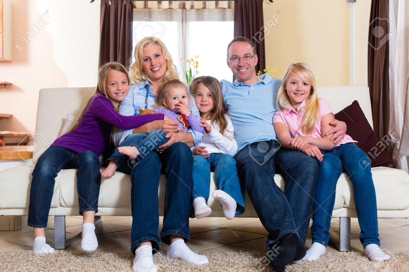 Family, father, mother and four sisters sitting on a couch in their living room Stock Photo - 15833389