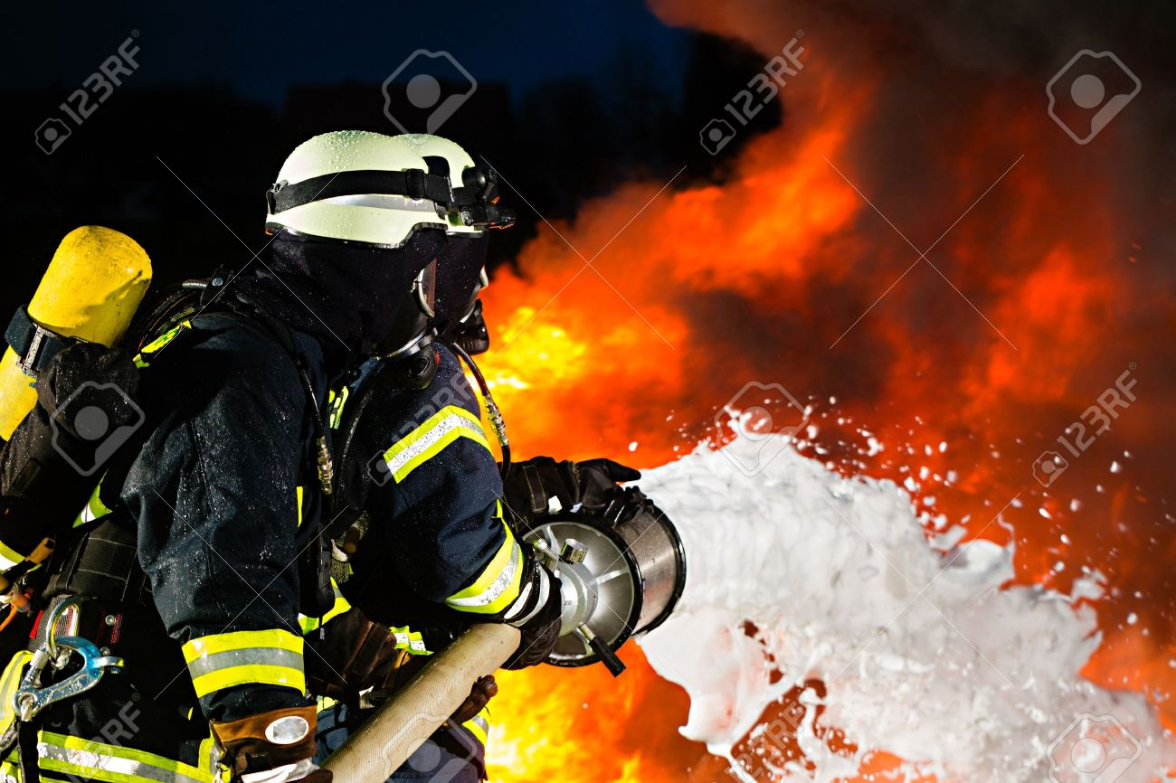 Firefighter - Firemen extinguishing a large blaze, they are standing with protective wear in front of wall of fire Stock Photo - 16883813