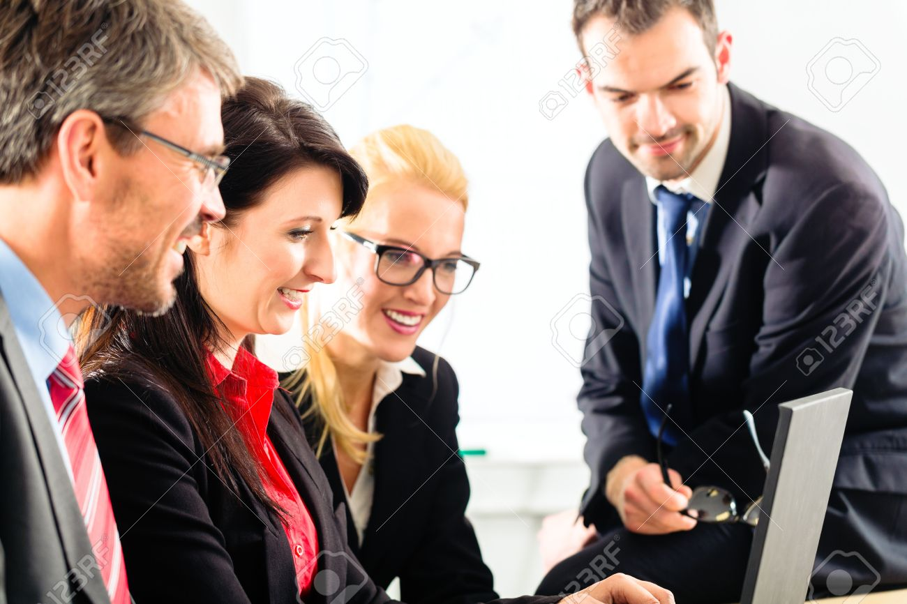 Four professionals in office in business attire looking at laptop screen working together Stock Photo - 16883362