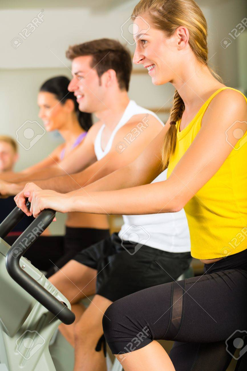 Group of men and women train on machine in a fitness club or gym Stock Photo - 17049502