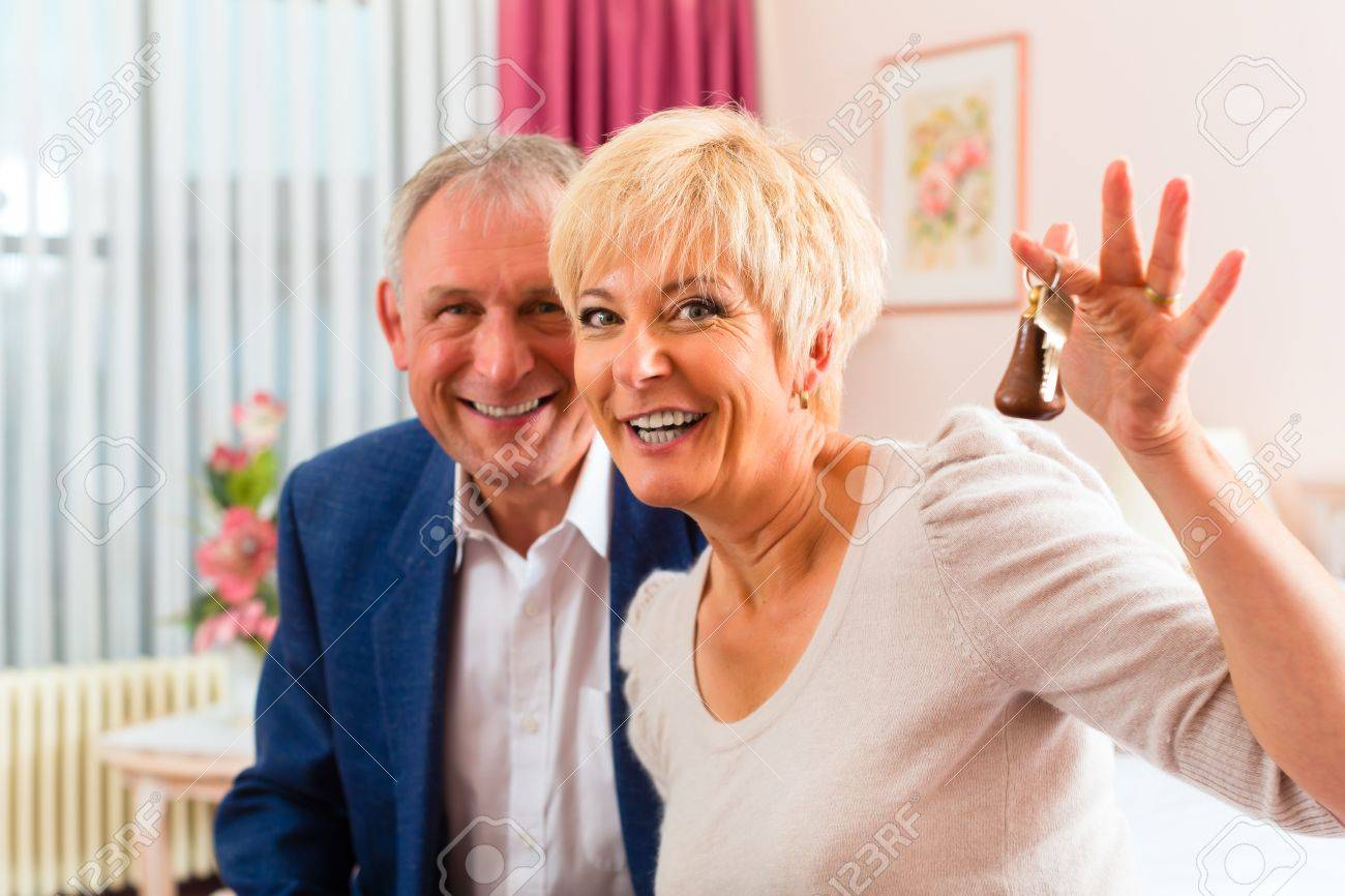 Senior couple sitting on the bed in the hotel room and the woman has a key in her hand Stock Photo - 17058459