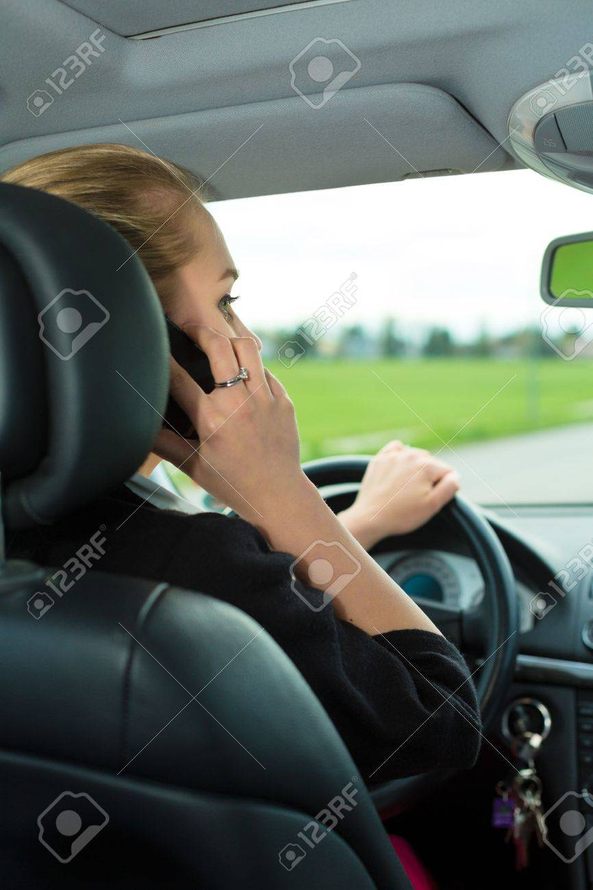 Young woman with telephone having phone conversation while driving car Stock Photo - 17108987