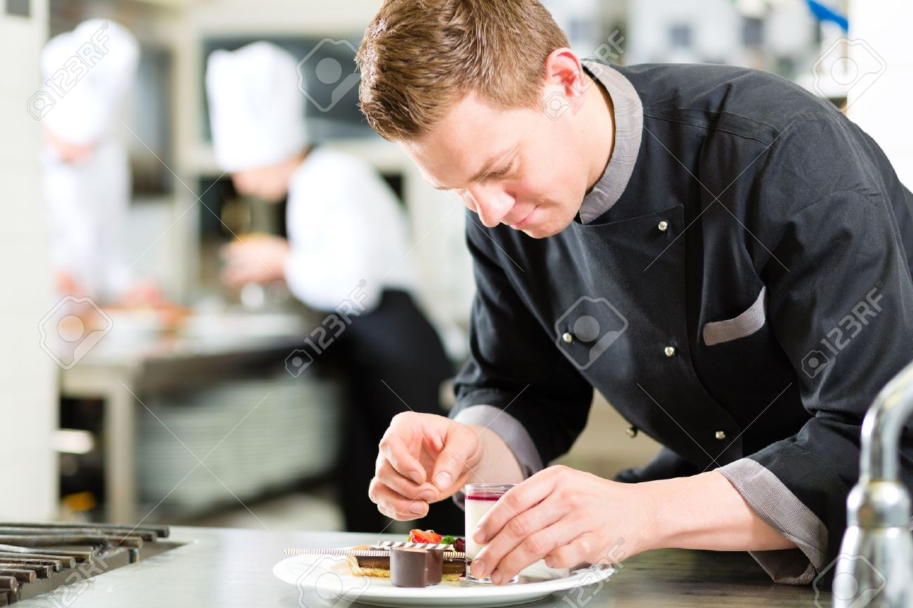 Cook, the pastry chef, in hotel or restaurant kitchen cooking, he is finishing a sweet dessert Stock Photo - 17109067