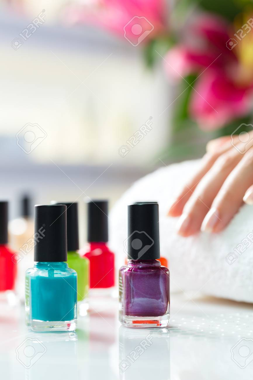Woman in a nail salon receiving a manicure, there are colorful nail polish Stock Photo - 17324710