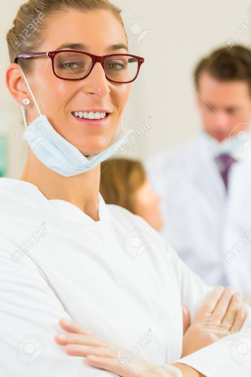 Dentists in her surgery looking at the viewer, in the background her colleague is giving a female patient a treatment Stock Photo - 17324705
