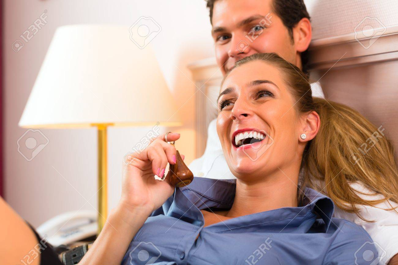 Young couple lying on the bed in the hotel room and the woman has a key in his hand Stock Photo - 17620255
