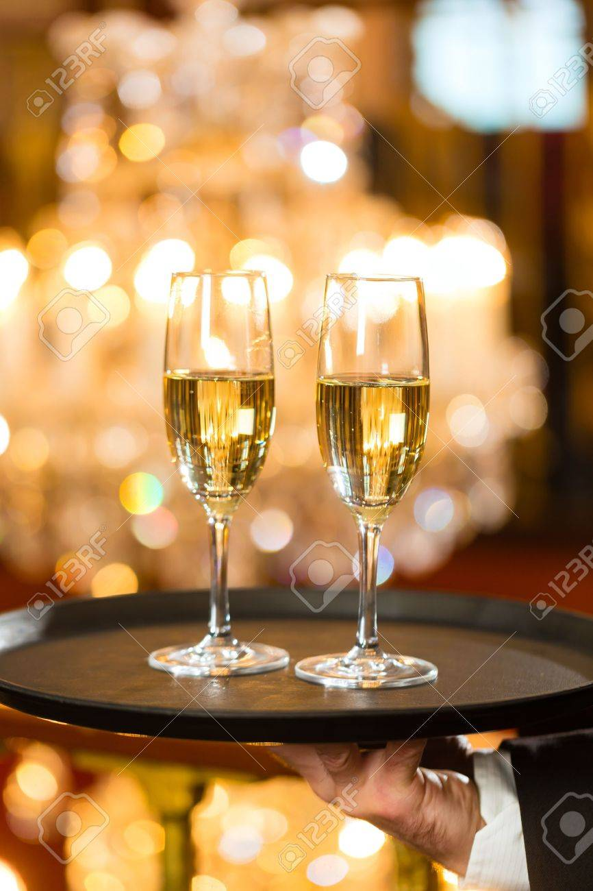 Waiter served champagne glasses on a tray in a fine dining waiter served champagne glasses on a tray in a fine dining restaurant a large chandelier arubaitofo Gallery
