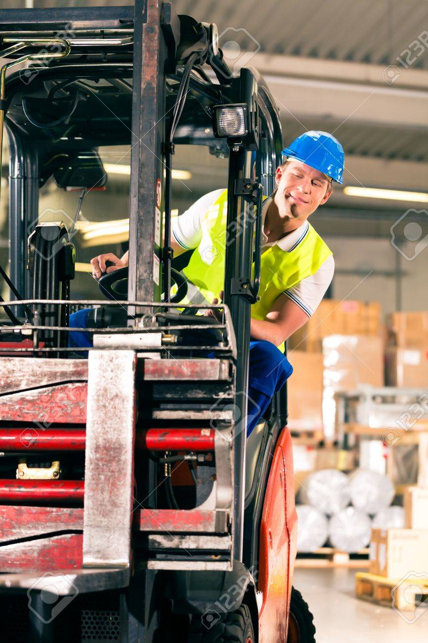 forklift driver in protective vest driving forklift at warehouse of freight forwarding company Stock Photo - 17657211