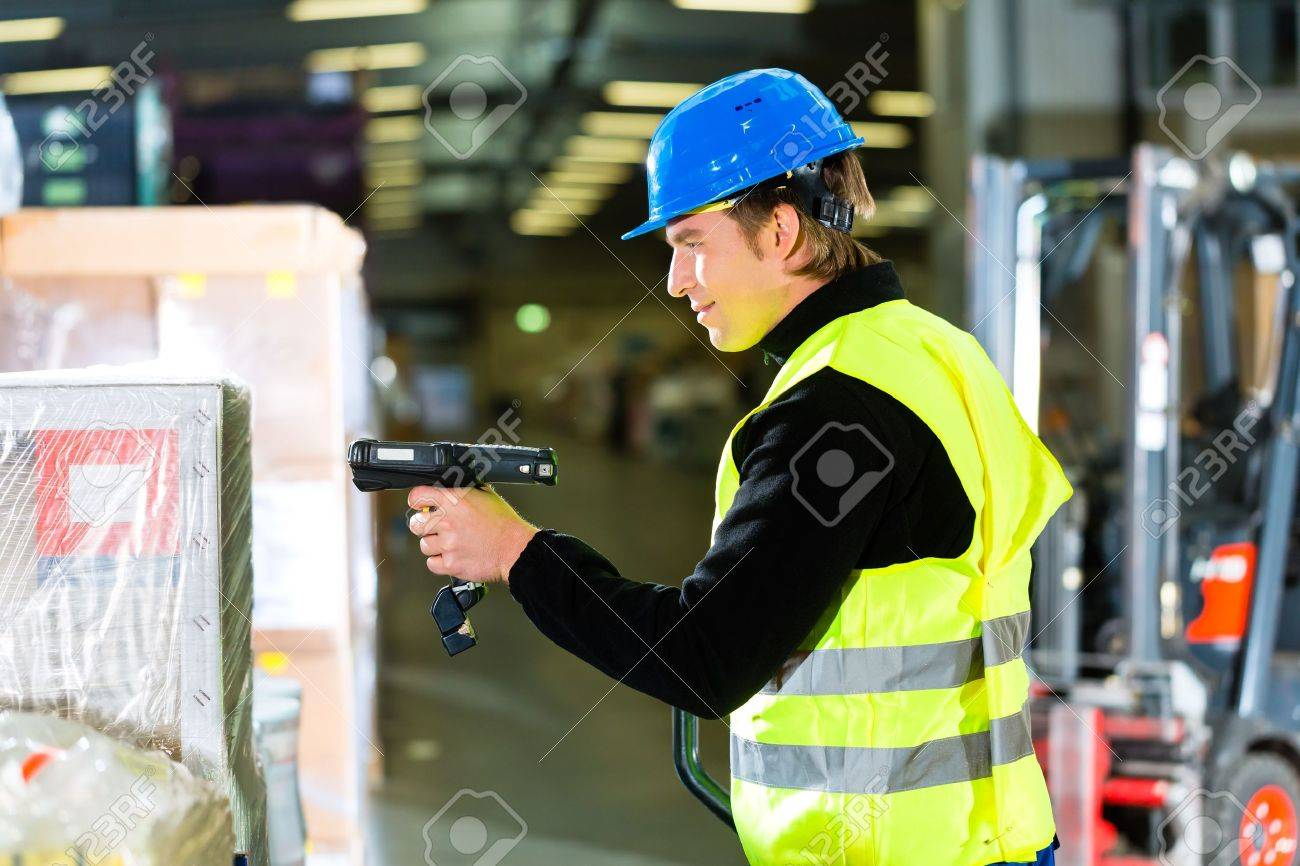 Warehouseman in protective vest using a scanner, standing beside packages and boxes at warehouse of freight forwarding company- a forklift is in Background Stock Photo - 17798529