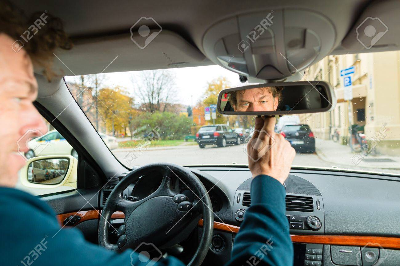 Experienced Taxi Driver Is Looking In The Rear View Mirror In His Taxi, He  Sets