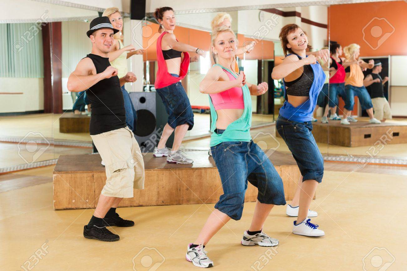 Zumba or Jazzdance - young people dancing in a studio or gym doing sports or practicing a dance number Stock Photo - 18165245