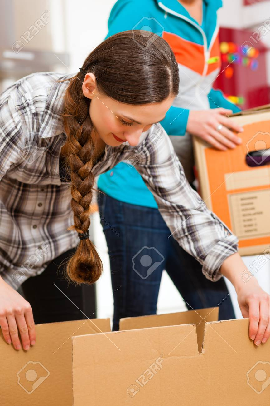 Young women - presumably friends - with moving box in her house moving in or out of a apartment, focus on moving box Stock Photo - 18153624