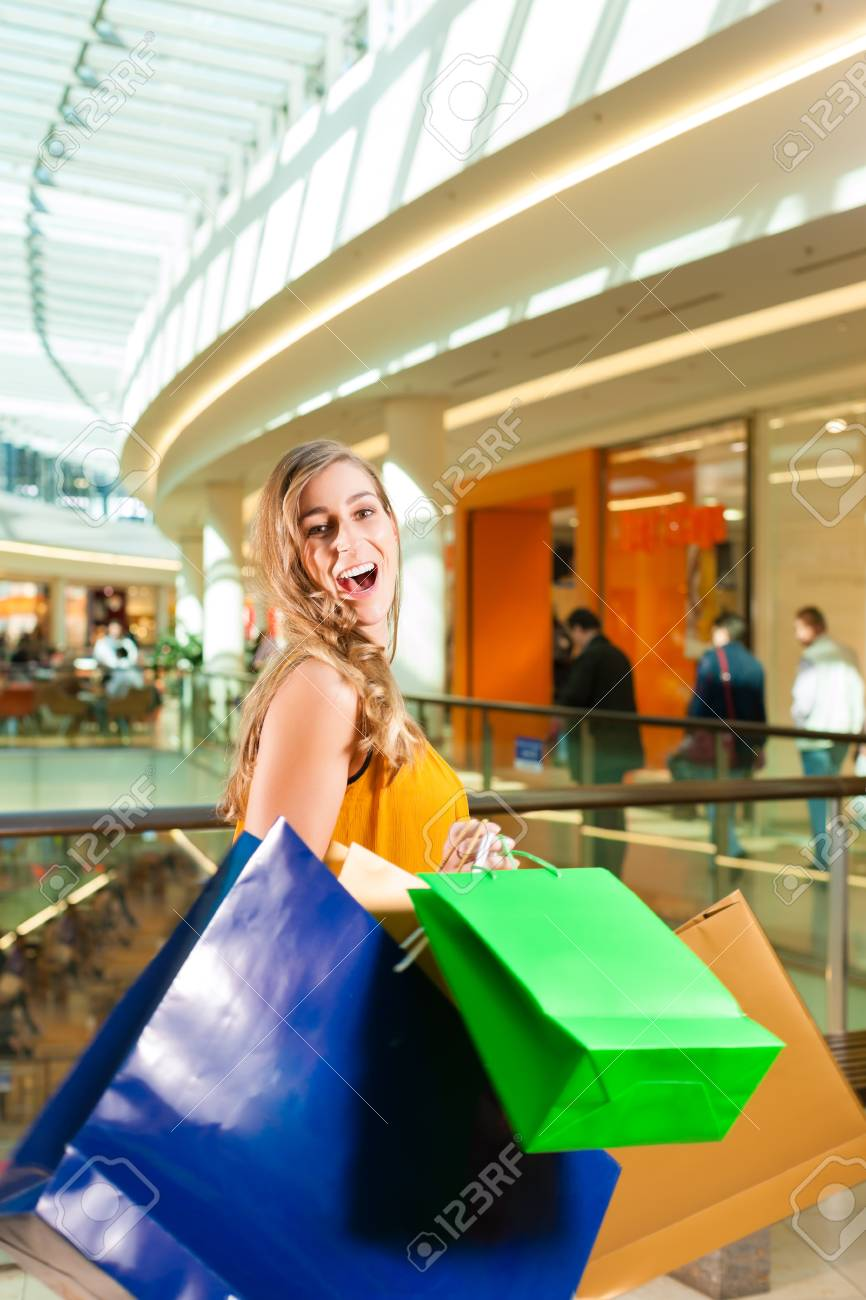 Young happy woman with shopping bags having fun while shopping in a mall Stock Photo - 18165156