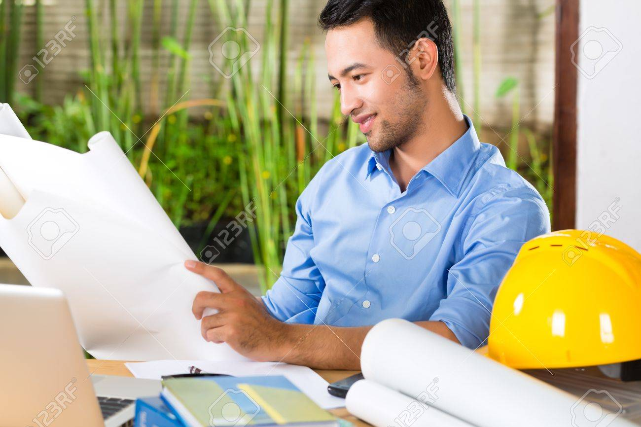 Freelancer - Architect working at home on a design or draft, on his desk are books, a laptop and a helmet or hard hat Stock Photo - 18165171