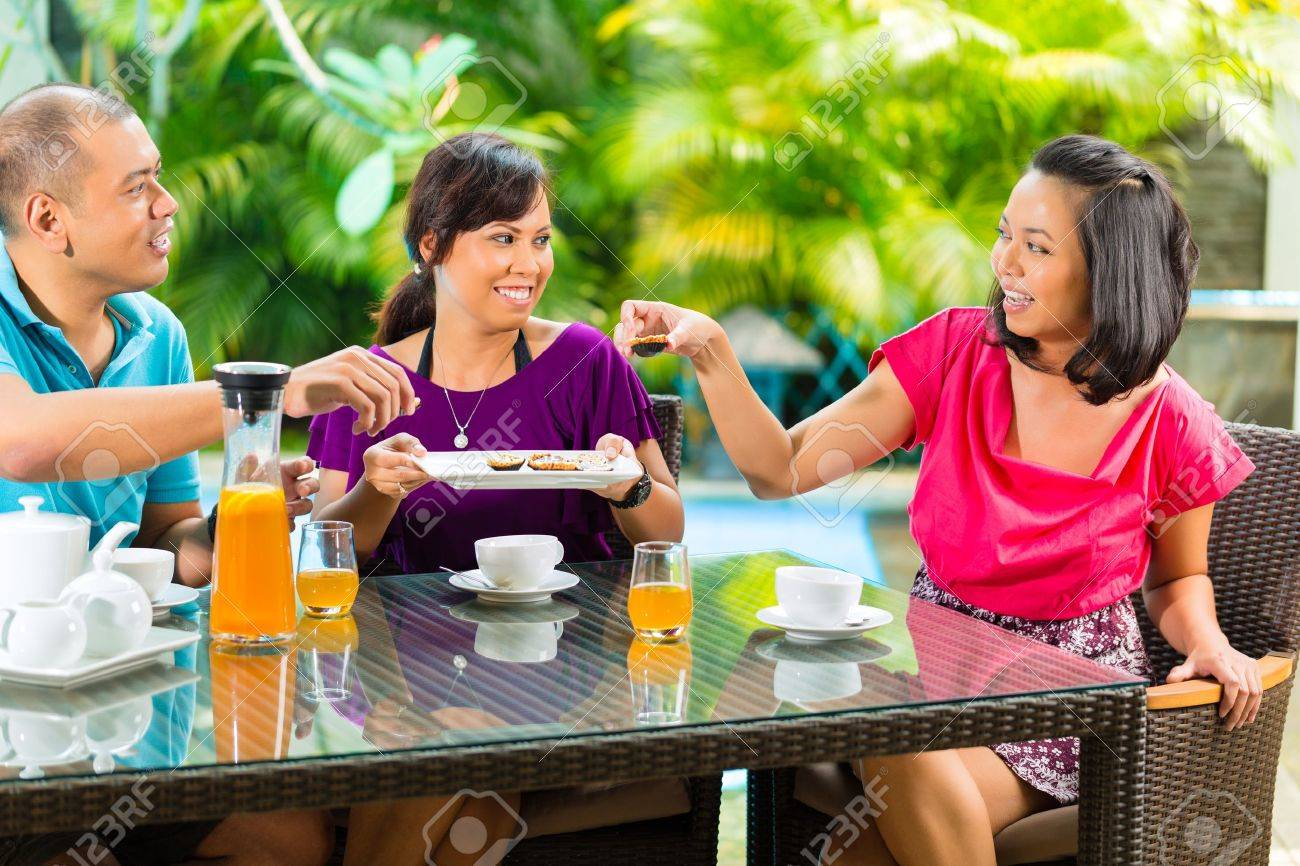 Asian friends having coffee on the porch in front of a home, in the background a tropical garden Stock Photo - 18344619