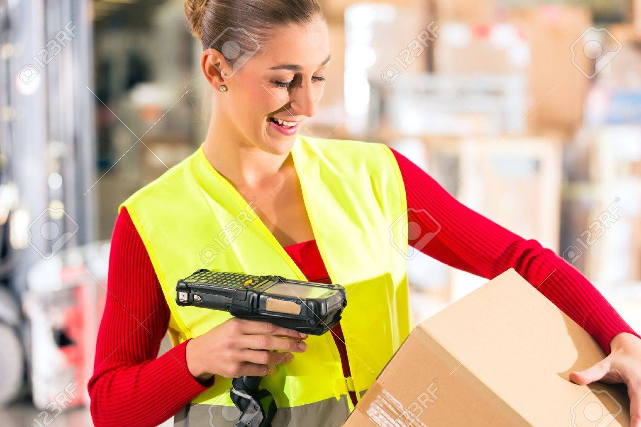 Female worker with protective vest and scanner, scans bar-code of package, standing at warehouse of freight forwarding company Stock Photo - 18452117