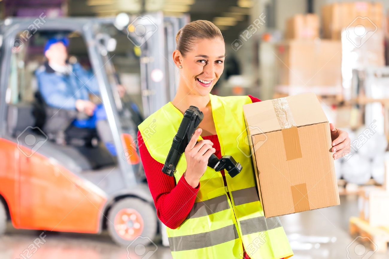 Female worker with protective vest and scanner, holds package, standing at warehouse of freight forwarding company, smiling Stock Photo - 18452147
