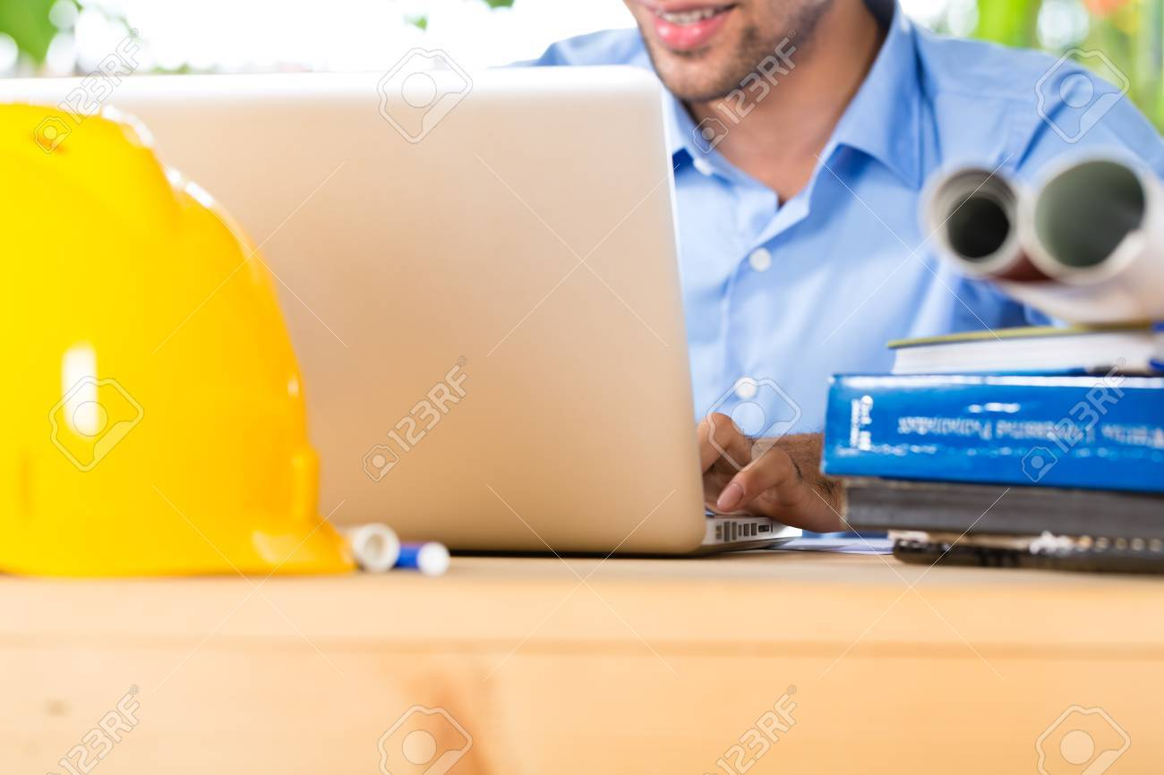 Freelancer - Architect working at home on a design or draft, on his desk are books, a laptop and a helmet or hard hat Stock Photo - 18452353