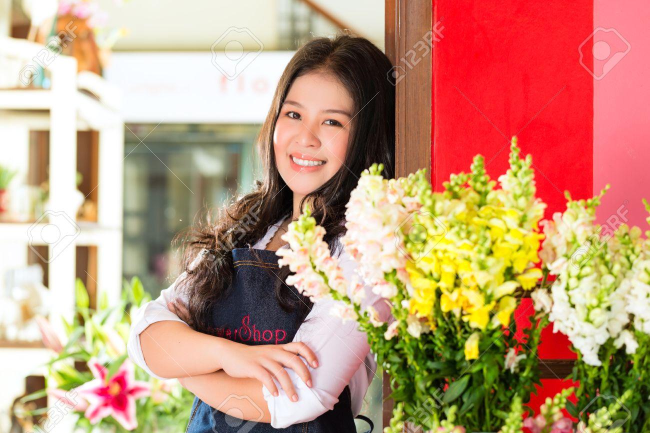 Friendly Asian florist or Saleswoman in a flower shop Stock Photo - 18559308