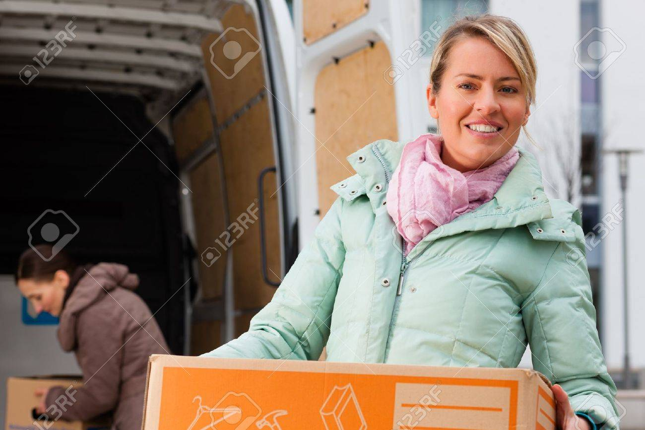 Two young women loading into a moving truck, they carry moving boxes Stock Photo - 18687131