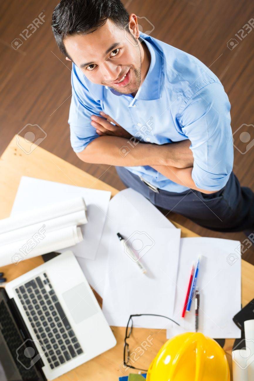 Freelancer - Architect working at home on a design or draft, on his desk are books, a laptop and a helmet or hard hat Stock Photo - 18687396