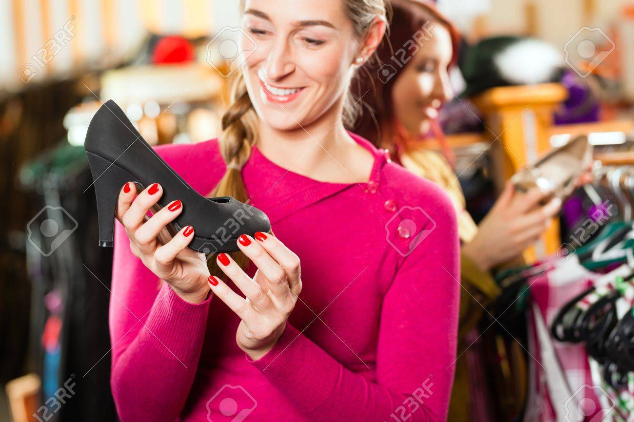 8f4bd6d256a Stock Photo - Traditional clothes - young woman is buying shoes for her  Tracht or dirndl in a shop
