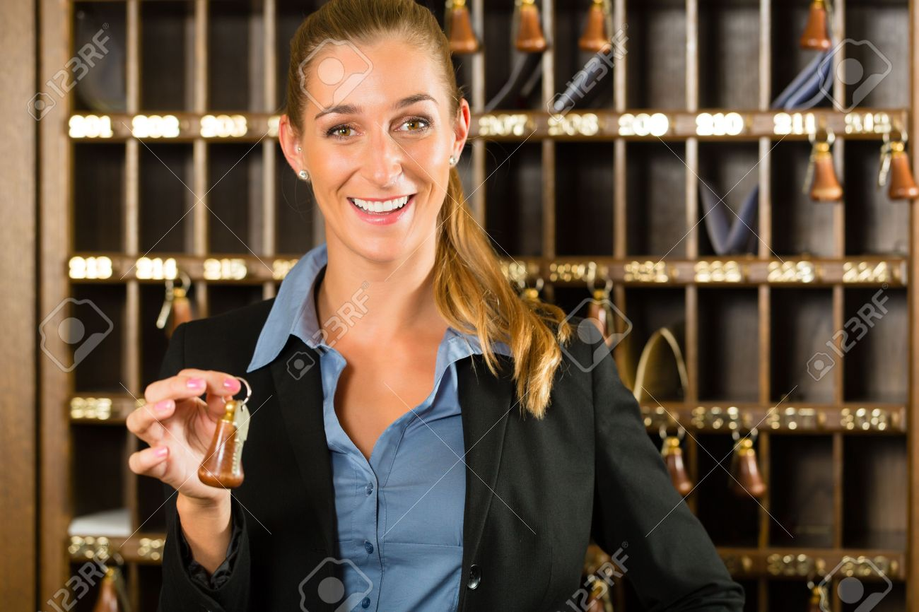Reception of hotel - desk clerk, woman holding a key in the hand and smiling Stock Photo - 19000765