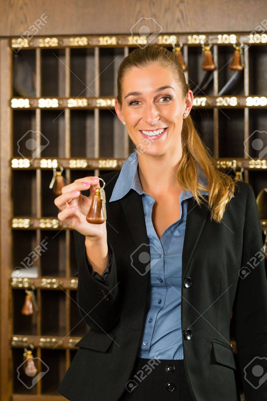 Reception of hotel - desk clerk, woman holding a key in the hand and smiling Stock Photo - 19000766